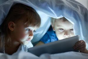 Niños escondidos en la cama mirando pantallas